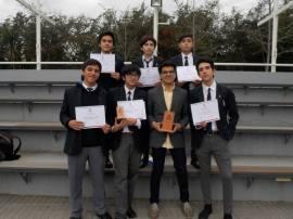 Los integrantes del equipo ganador, junto a su capitán, mostrando sus diplomas y trofeos.
